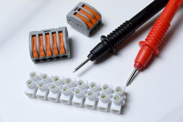 Blocos terminais elétricos e pontas de prova do multímetro em um fundo claro. fechar-se.