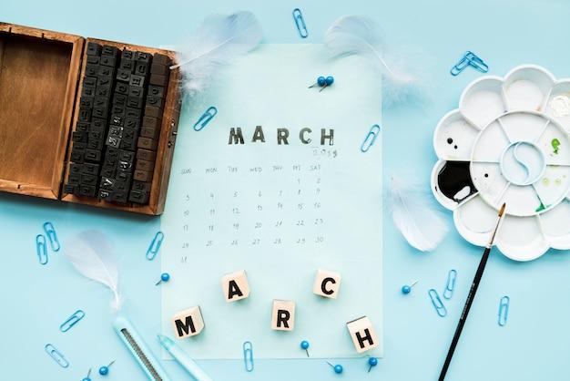 Blocos tipográficos de madeira; pena; blocos de março e carimbo de março no calendário com artigos de papelaria contra o pano de fundo azul