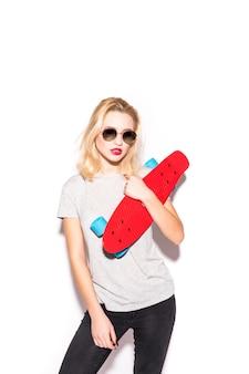 Blodnie linda garota skatista em óculos de sol brilhantes fica em frente a parede branca