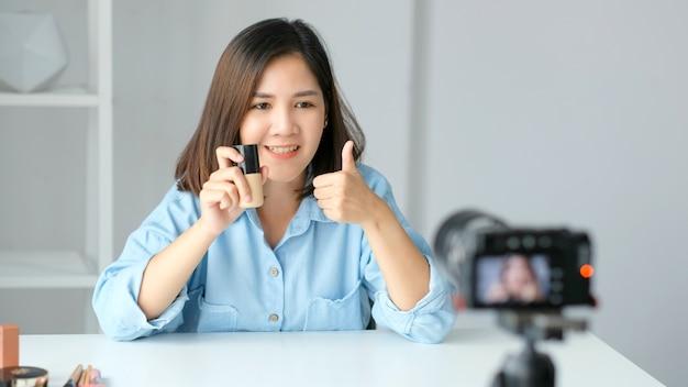 Blog de beleza, jovem blogueira asiática gravando tutoria de vídeo de maquiagem com produtos de beleza em casa
