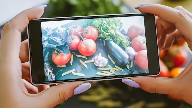 Blog de comida. nutrição saudável. mulher tirando foto de macarrão de legumes frescos na câmera do smartphone.