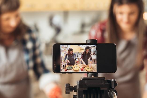 Blog de culinária. duas mulheres gravando um vídeo com eles na cozinha usando o telefone no tripé