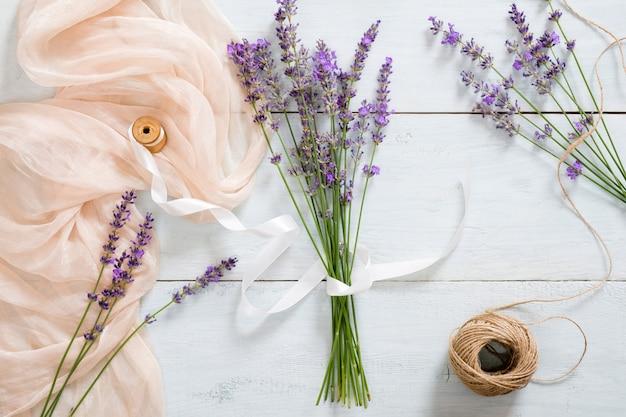 Blog de moda mesa elegante com ramo de flores de lavanda com fita, cobertor rosa pastel, barbante
