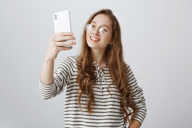 Blog de registro de garota fofa sorridente, tirando selfie no smartphone