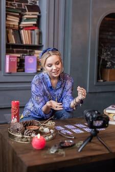 Blog de vídeo. jovem simpática falando sobre itens mágicos enquanto tem seu próprio videoblog