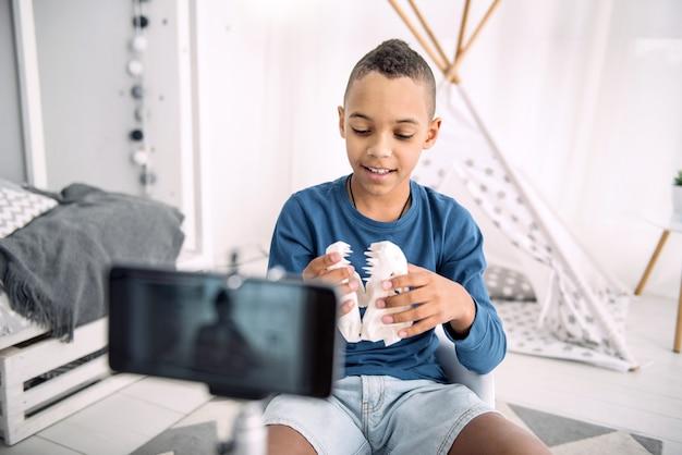 Blog online. menino blogueiro afro-americano inteligente examinando o modelo da mandíbula enquanto grava um vídeo