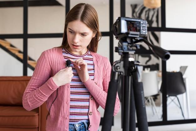 Blogger ajustando o microfone na frente da câmera