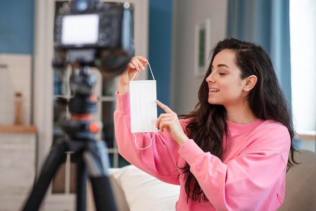 Blogger, apontando para a máscara cirúrgica na frente da câmera