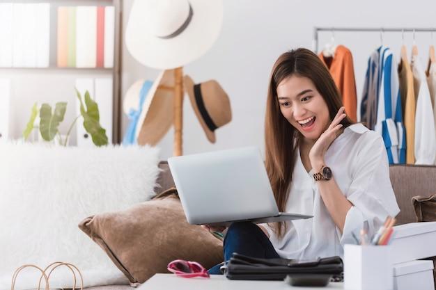 Blogger asiático de sorriso bonito do desenhador de moda da mulher que senta-se na loja de roupa.