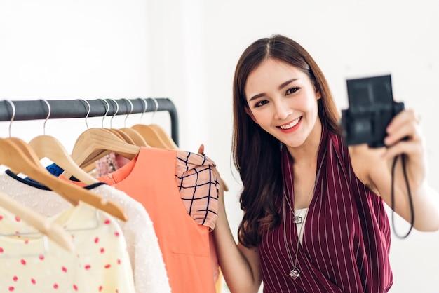 Blogger asiático jovem bonita em frente a câmera, gravando-se comprando e escolhendo roupas em uma loja. compras de moda e conceito de mídia social
