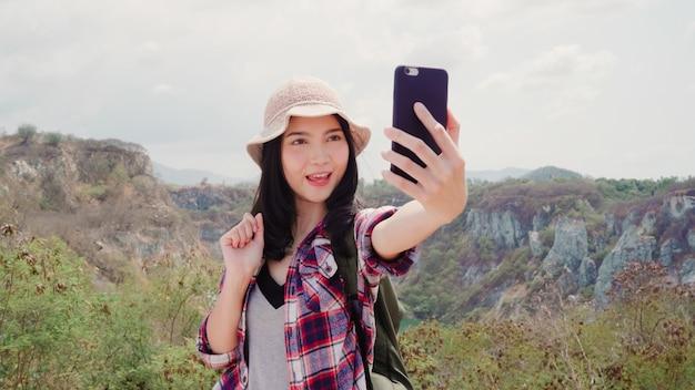 Blogger asiático mulher mochileiro registro vlog vídeo no topo da montanha