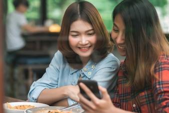Blogger bonito feliz das mulheres asiáticas dos amigos que usa a foto do smartphone e que faz o vídeo do vlog do alimento