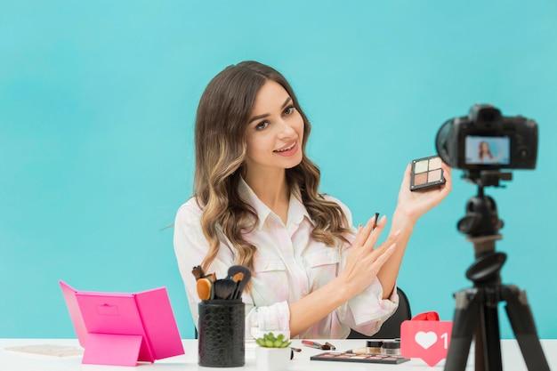 Blogger bonito gravando vídeo de maquiagem