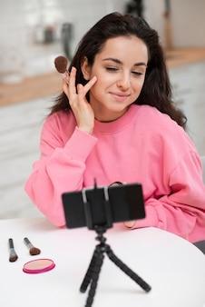 Blogger colocando maquiagem e gravando