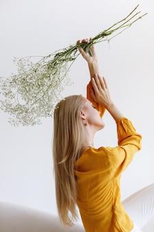Blogger com flores secas em um fundo cinza. foto estilosa