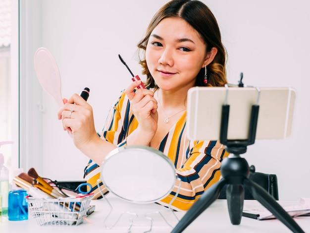 Blogger consideravelmente asiático da mulher a revisão em linha cosmética