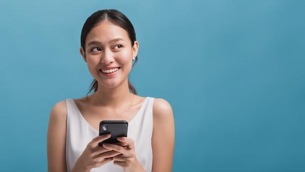 Blogger de mulheres bonitas felizes asiáticas sorrindo e segurando o smartphone isolado em fundo azul