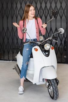 Blogger de tiro completo gravando-se sentado em sua moto