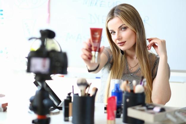Blogger de vídeo feminino presente cosméticos novos. blogging negócios, conceito de comércio eletrônico. menina bonita caucasiana segurando a base ou creme para a pele. maquillage artist gravação maquiagem blog