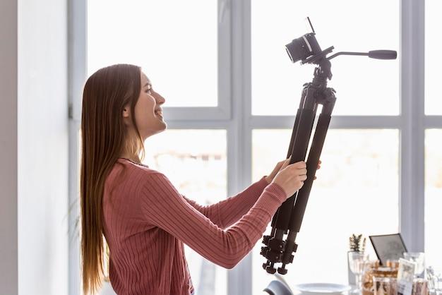 Blogger de vista lateral segurando o tripé com câmera