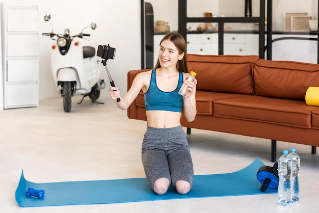 Blogger desportivo segurando a garrafa de água e usando o smartphone