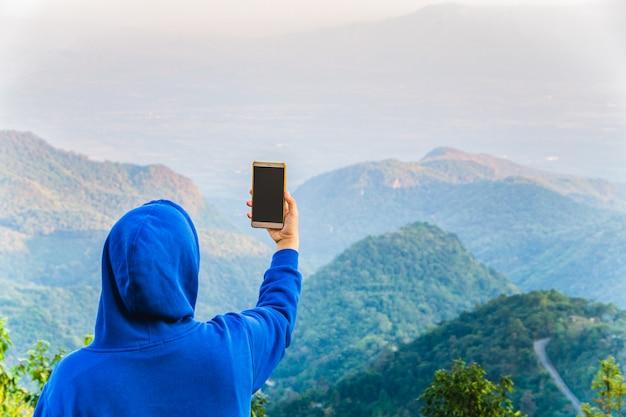 Blogger do moderno que usa o telefone esperto que toma a foto no auge da montanha de doi angkhang, chiangmai, tailândia.