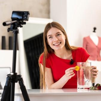 Blogger feliz mostrando o tutorial de decoração diy na câmera