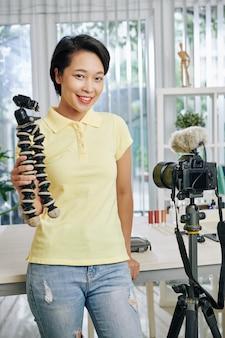 Blogger feminino com tripé