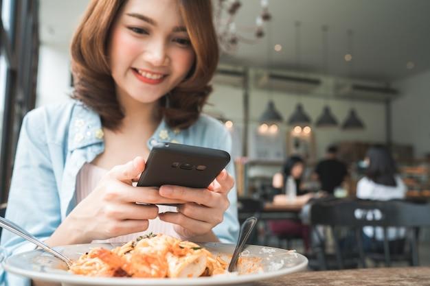Blogger feminino fotografando o almoço no restaurante com o telefone dela