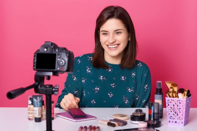 Blogger feminino senta-se à mesa com muitos produtos cosméticos, grava vídeo tutorial