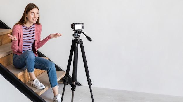 Blogger gravando com a câmera e sentado na escada