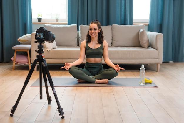 Blogger gravando sessão de yoga em casa