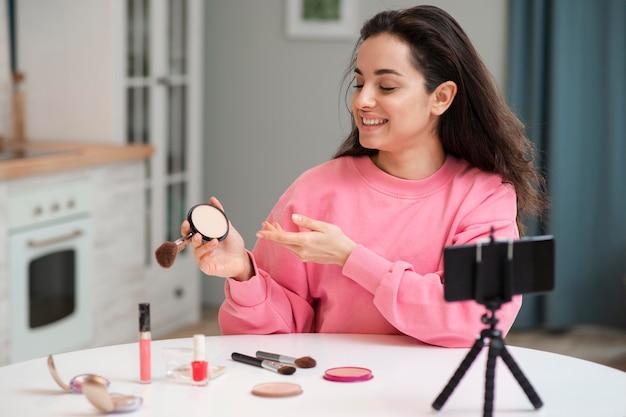 Blogger gravando vídeo com acessórios de maquiagem