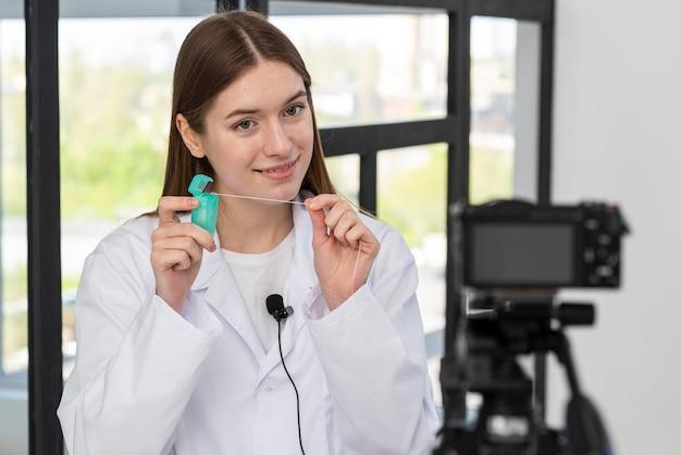 Blogger gravando vídeo com fio dental