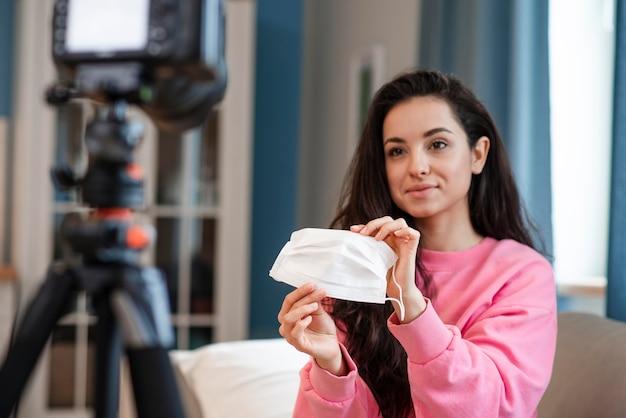 Blogger gravando vídeo com máscara cirúrgica