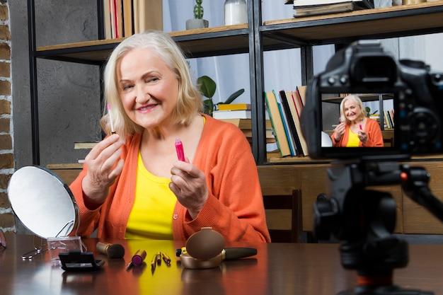 Blogger idoso da mulher que a grava fazendo compo o vídeo em linha pela câmera,