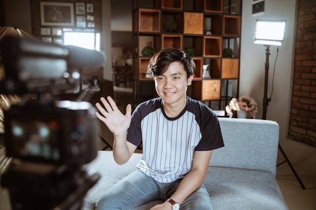 Blogger jovem asiático fazer revisão usando a câmera em primeiro plano