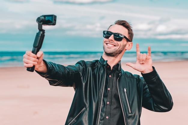 Blogger jovem em óculos de sol fazendo selfie ou streaming de vídeo na praia usando câmera de ação com estabilizador de câmera gimbal.