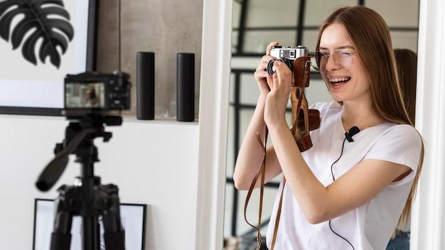 Blogger jovem gravação com câmera profissional, segurando uma câmera retro