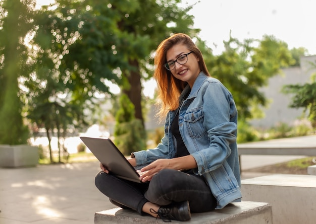 Blogger jovem mulher moderna em uma jaqueta jeans e óculos tem um laptop nas mãos no parque. aprendizagem on-line, blogs