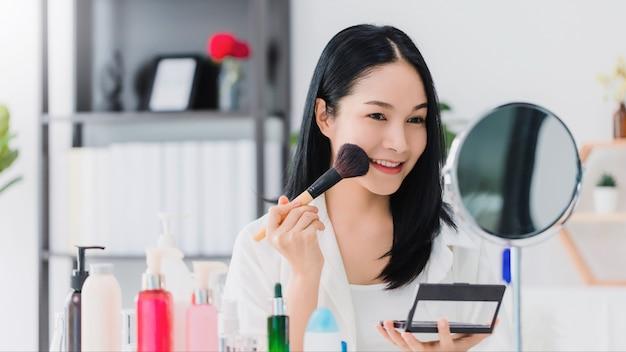 Blogger linda mulher asiática está mostrando como fazer as pazes e usar cosméticos.