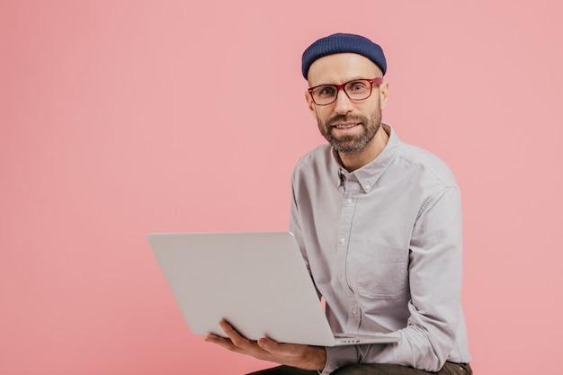 Blogger masculino com barba atualiza seu perfil, navega em redes sociais, compartilha arquivos multimídia com seguidores