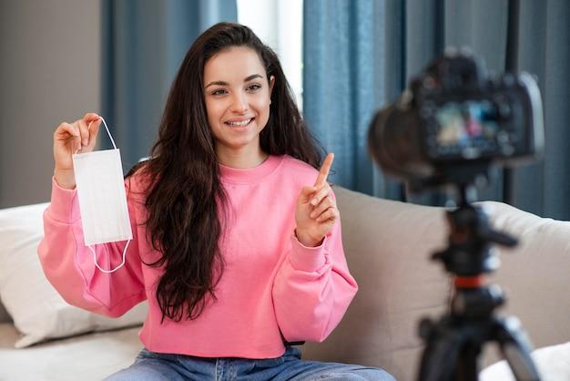 Blogger mostrando a máscara cirúrgica na câmera