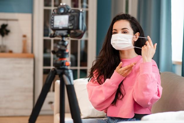 Blogger mostrando como colocar a máscara cirúrgica