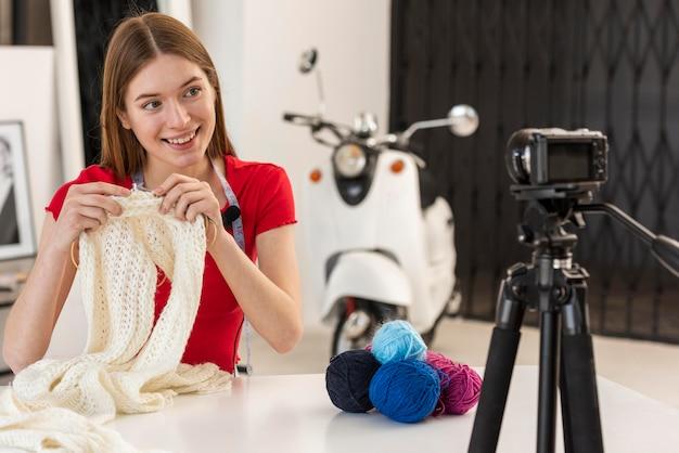 Blogger mostrando como tricotar na câmera