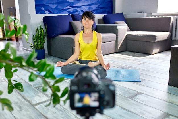 Blogger mulher sênior com forma de corpo magro no sportswear fazendo yoga em casa.