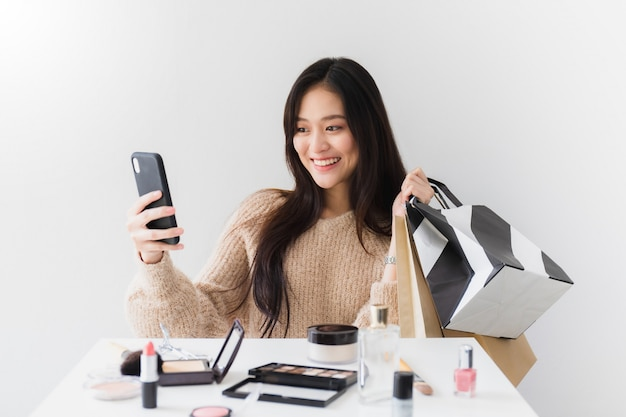 Blogger mulheres asiáticas bonitas estão usando o smartphone ao vivo on-line com um shoppi