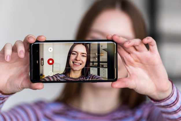 Blogger segurando o telefone e gravando a si mesma