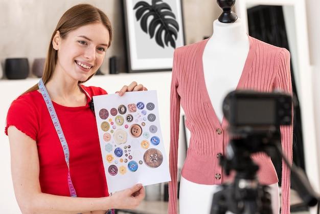 Blogger segurando papel com botões coloridos