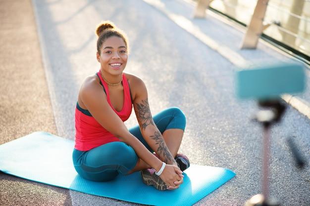 Blogger sentado. blogueiro de esportes famoso lindo sentado no tapete de esporte depois de praticar ioga